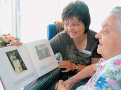 Fotos aus ihrem Leben sind ein wichtiger Zugang zu Menschen mit Demenz. Ursula Fischer, examinierte Altenpflegerin und Gerontopsychiatrische Fachkraft, mit einer Bewohnerin des Evangelischen Altenheims St. Johannisstift.