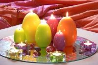 Auf einem Spiegelteller platziert, wird die farbenprächtige Osterdeko im Handumdrehen zum strahlenden Mittelpunkt des Raumes. Foto: Gütegemeinschaft Kerzen