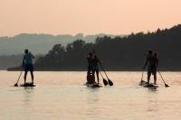 Tipp für einen Sommerabend am Chiemsee: Entspannen auf dem Stand-Up-Paddling-Board, danach kann man in einer Beach-Bar chillen. Foto: djd | Chiemsee-Alpenland Tourismus